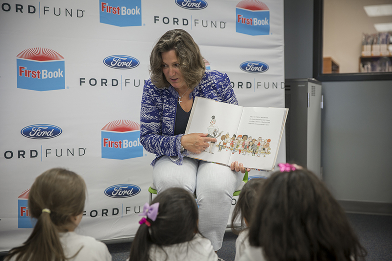 Ford holding book reading to small group