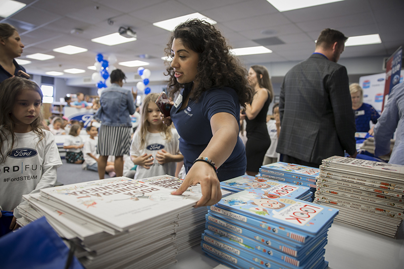 Ford Fund employee handing out books