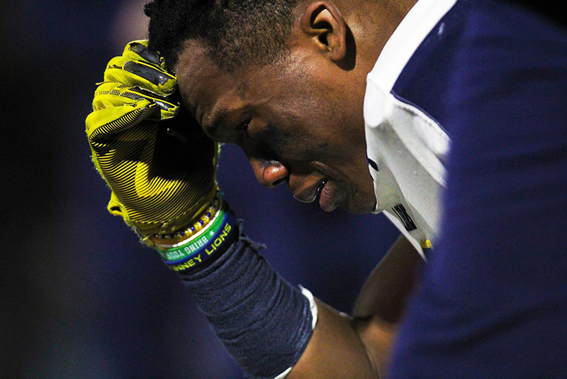close up of player squatting with head in hand crying