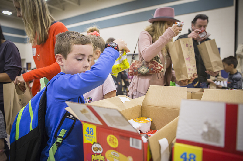 boy picking up chips out of a box in a line