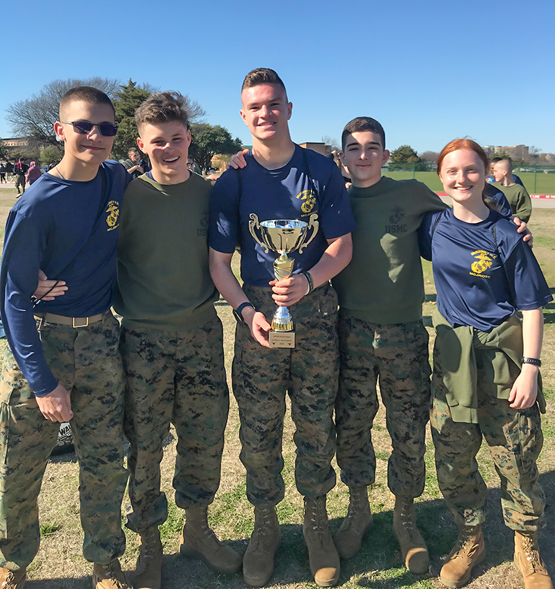 group standing with arms around each other holding trophy