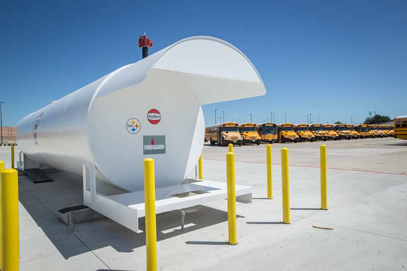white fuel tank with buses in background