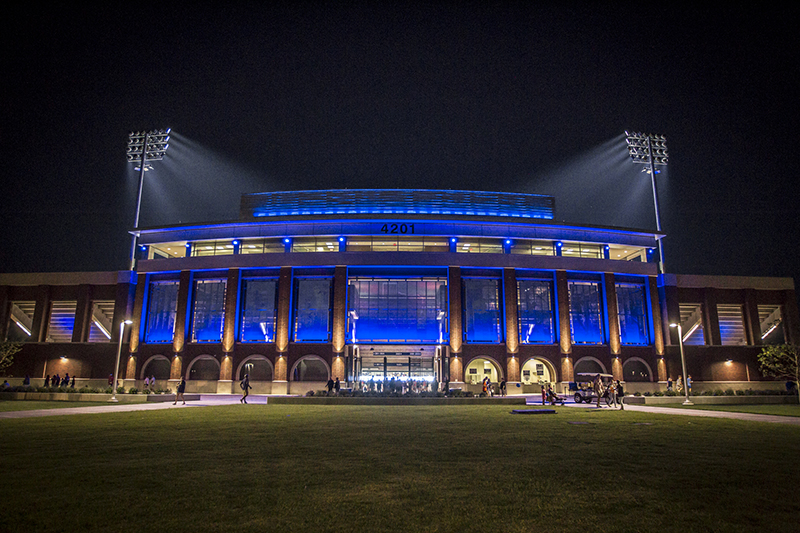 night time exterior view of stadium lit up with blue