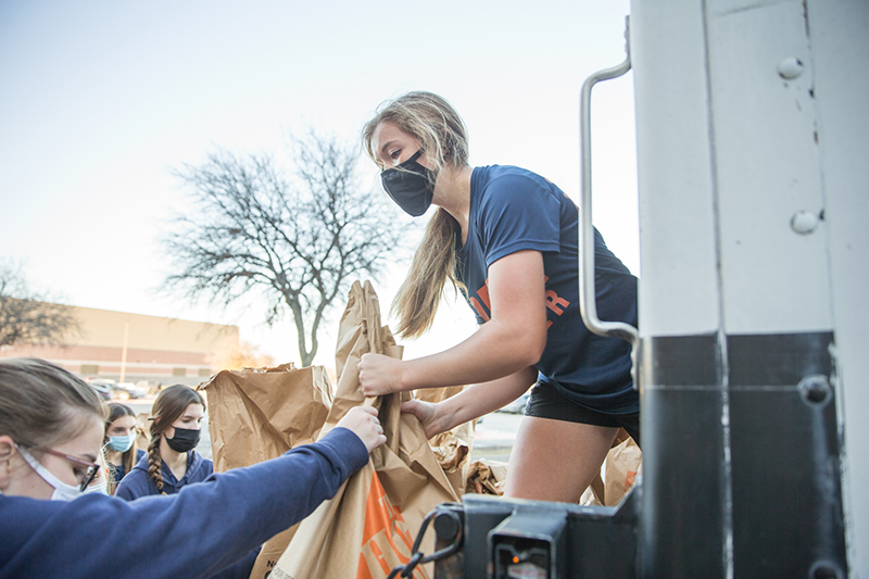 female student lifting bag onto back of truck