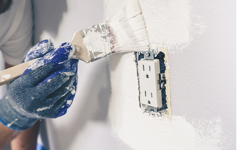 Painter man with gloves painting the wall around power outlet.