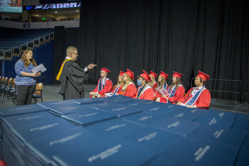 grads on stage receiving instructions before ceremony