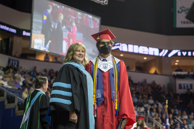 peirson posing with male graduate at side of the stage