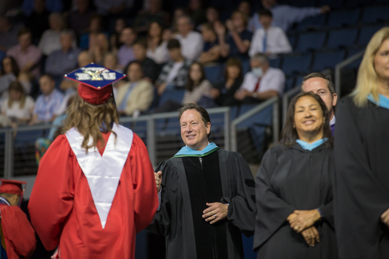 McDaniel smiling and giving a graduate a fist bump