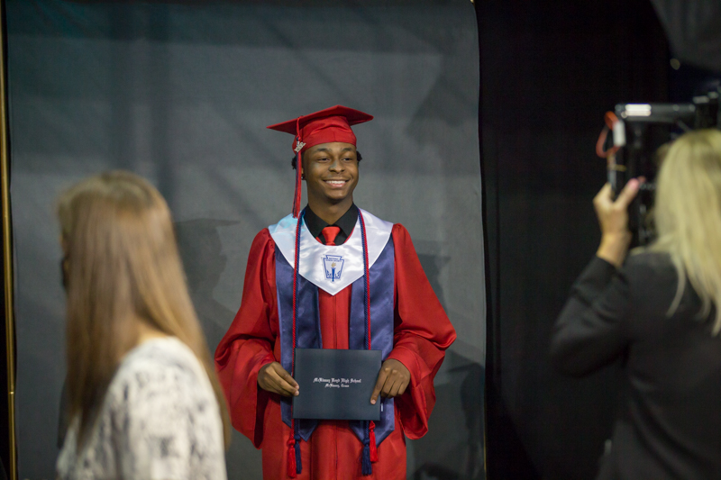 male student getting picture taken with diploma