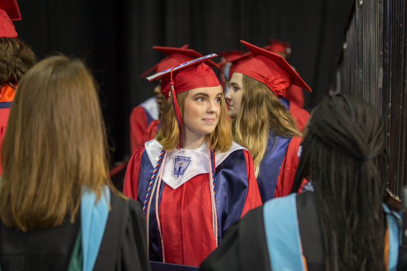 female student looking back at stage in line