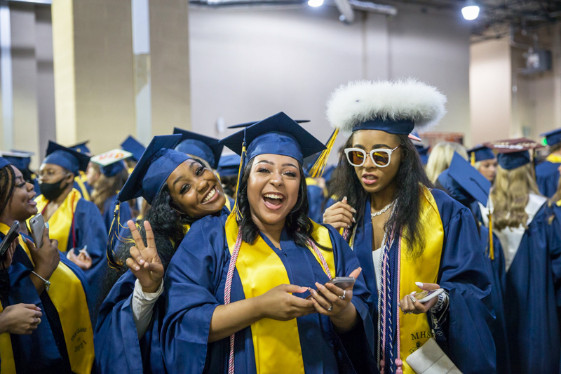 female graduates backstage laughing and taking selfies