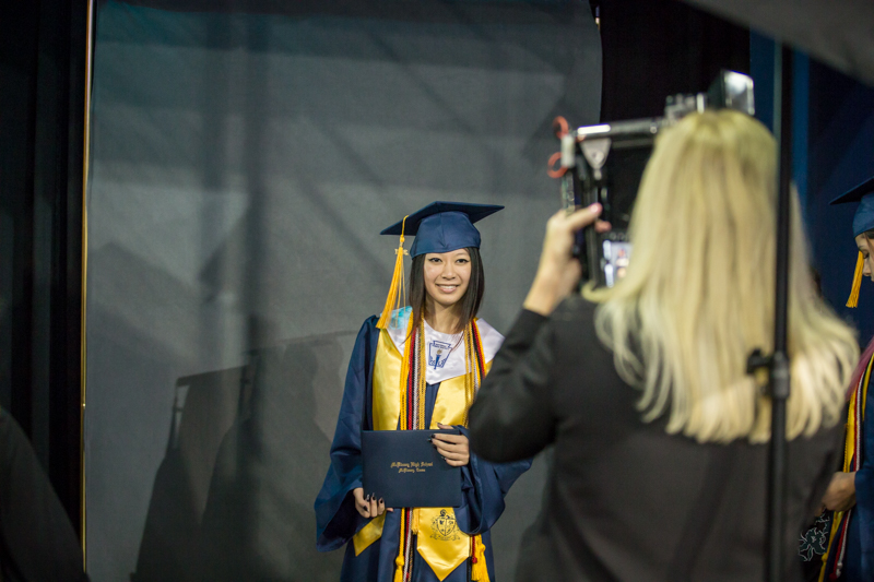 female student poses for photo with diploma