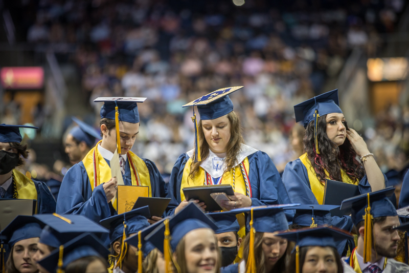 students standing and looking at diplomas in front of their seats