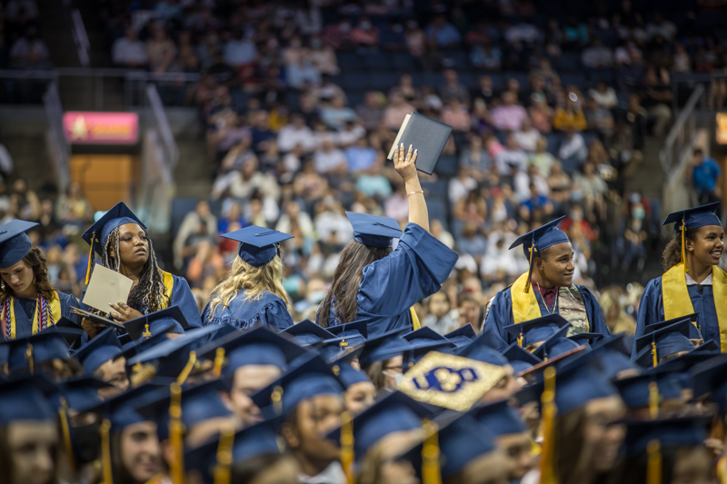 student holding up diploma, looking back toward audience