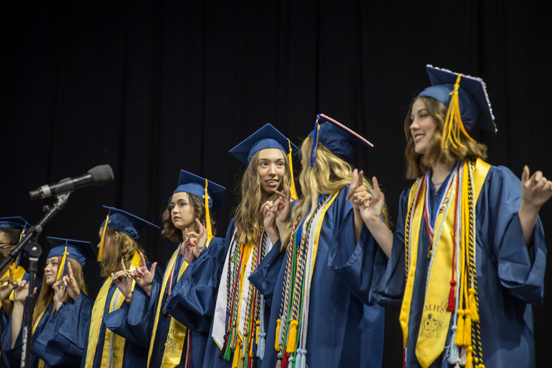 female graduates look at each other before the start of the school song