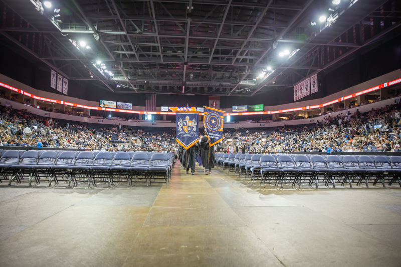 view of empty graduate seats as banners are brought down the middle aisle ahead of graduates