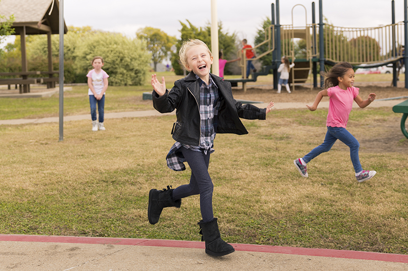 girl laughing and running on playground