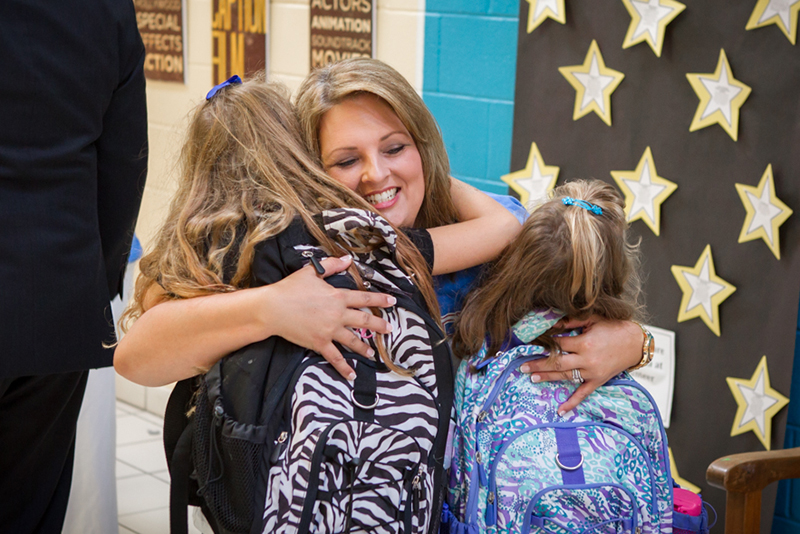 Principal Michelle Baumann hugging two young students on first day of school
