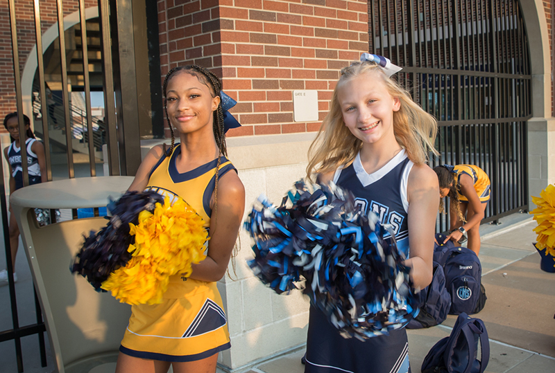 two cheerleaders smiling for camera