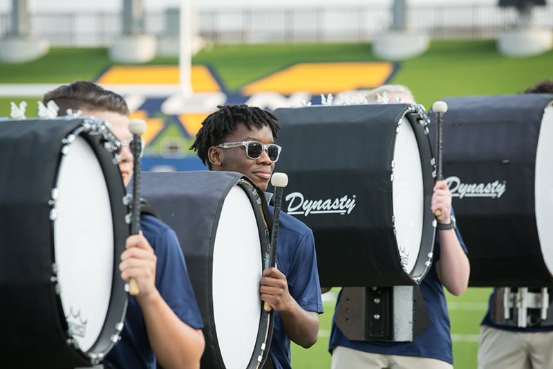 bass drum players in a line waiting to play