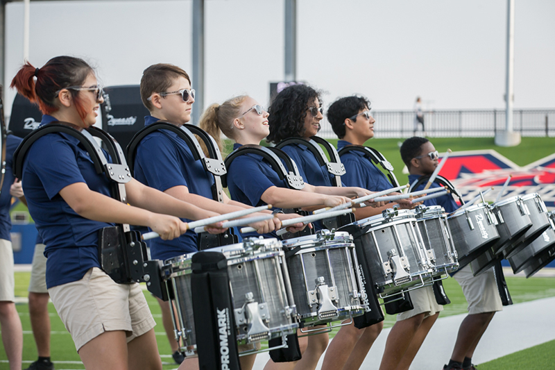 line of student drummers performing on sideline