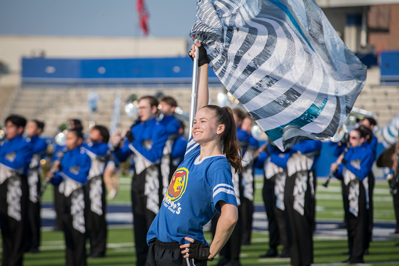 Color guard girl posing with flag during performance