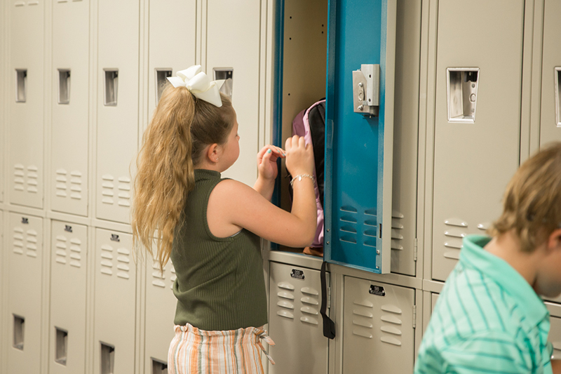 young female student placing backpack in locker