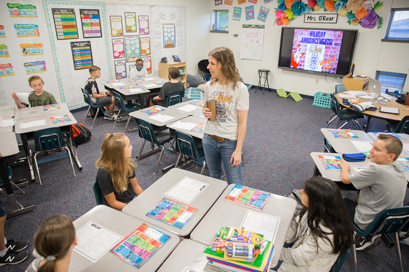 Teacher standing in middle of class talking with students