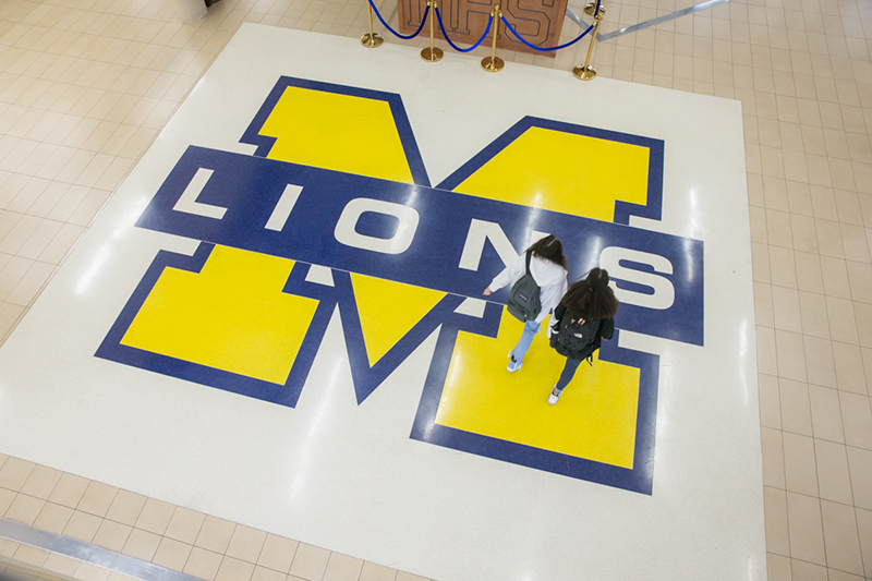overhead view of two female students walking across school logo in common area