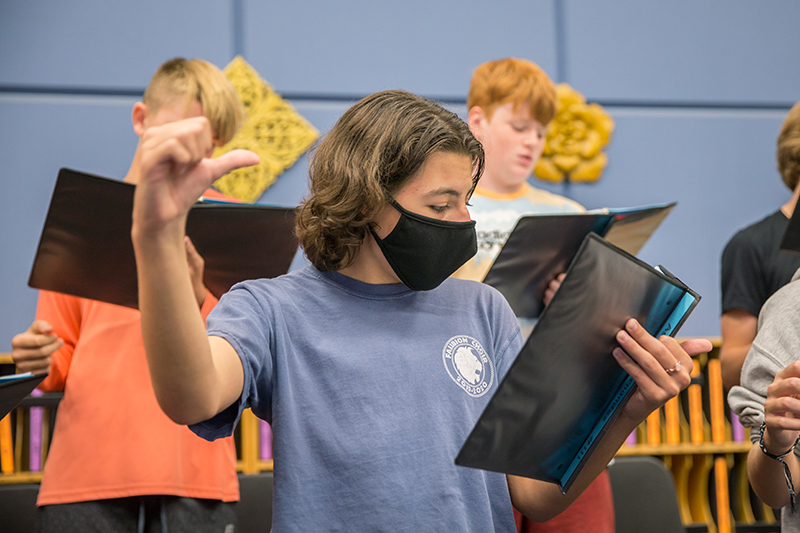 student singing in choir with mask on and making hand gesture