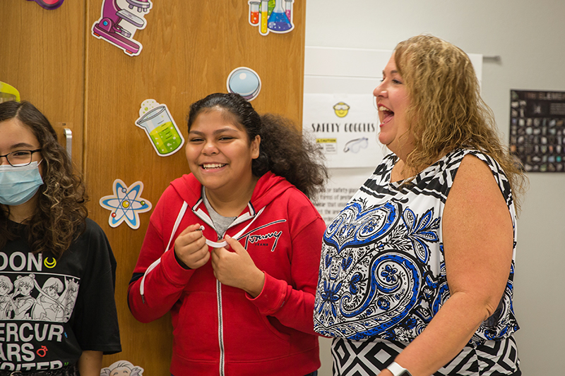 Rogers in a classroom laughing with students
