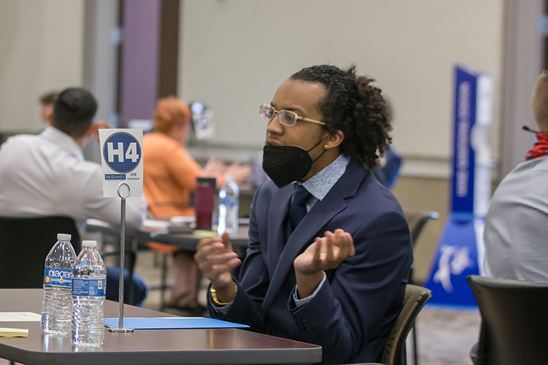 male Black student talking at table